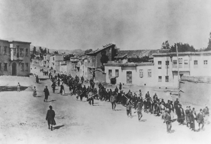 Ottoman military forces march Armenian men from Kharput to an execution site outside the city. Kharput, Ottoman Empire, March – June 1915. Armenian National Institute.