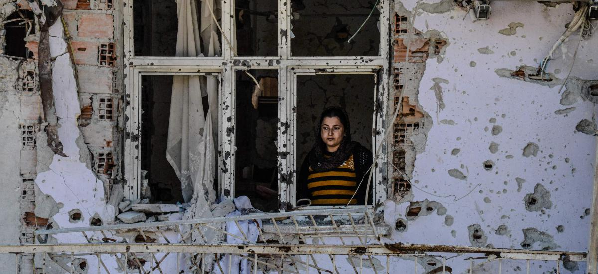 A woman looks through a window of her ruined house on March 8, 2016 during International Women`s day in Cizre district. AFP / ILYAS AKENGIN