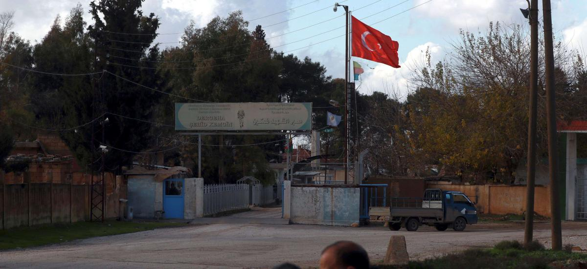 People are pictured sitting in the Syrian town of Darbasiyah on December 13, 2018 as the Turkish flag flutters on the opposite side of the border crossing with Turkey. (Photo by Delil SOULEIMAN / AFP)