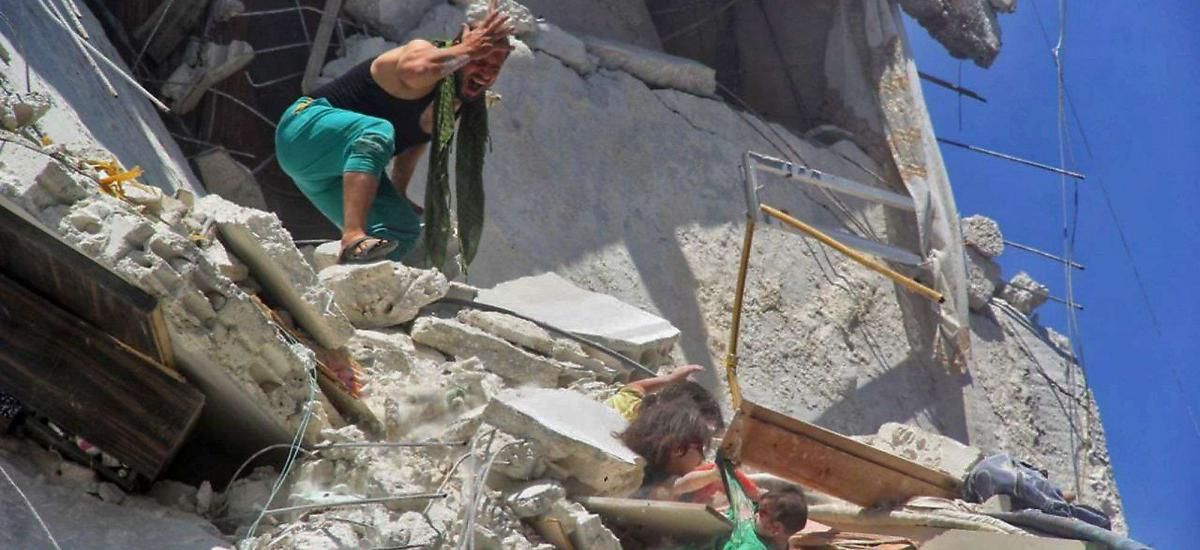 An image grab taken from a video by Syrian news website SY24 on July 25, 2019 shows a Syrian man trying to save two Syrian girls from a bombed-out building in Idlib.