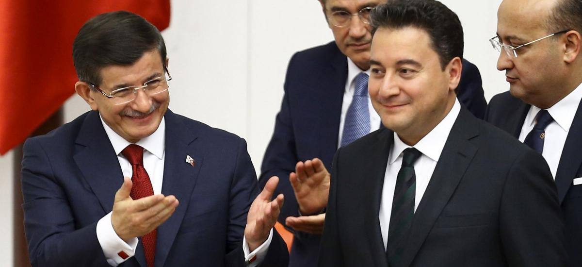 Turkey's Prime Minister Ahmet Davutoglu (L), accompanied by his deputy Ali Babacan, greets parliamentarians during a swearing-in ceremony, June 23, 2015. REUTERS/Umit Bektas