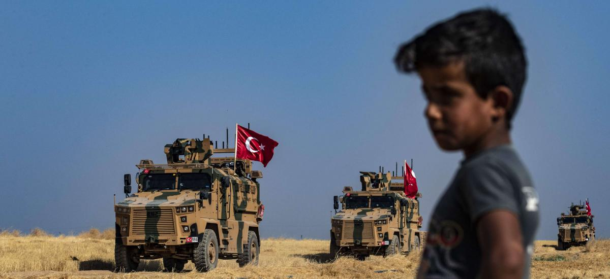 A Syrian boy watches as Turkish military vehicles, part of a US military convoy, take part in joint patrol in the Syrian village of al-Hashisha on the outskirts of Tal Abyad town along the border with Turkey, on October 4, 2019.