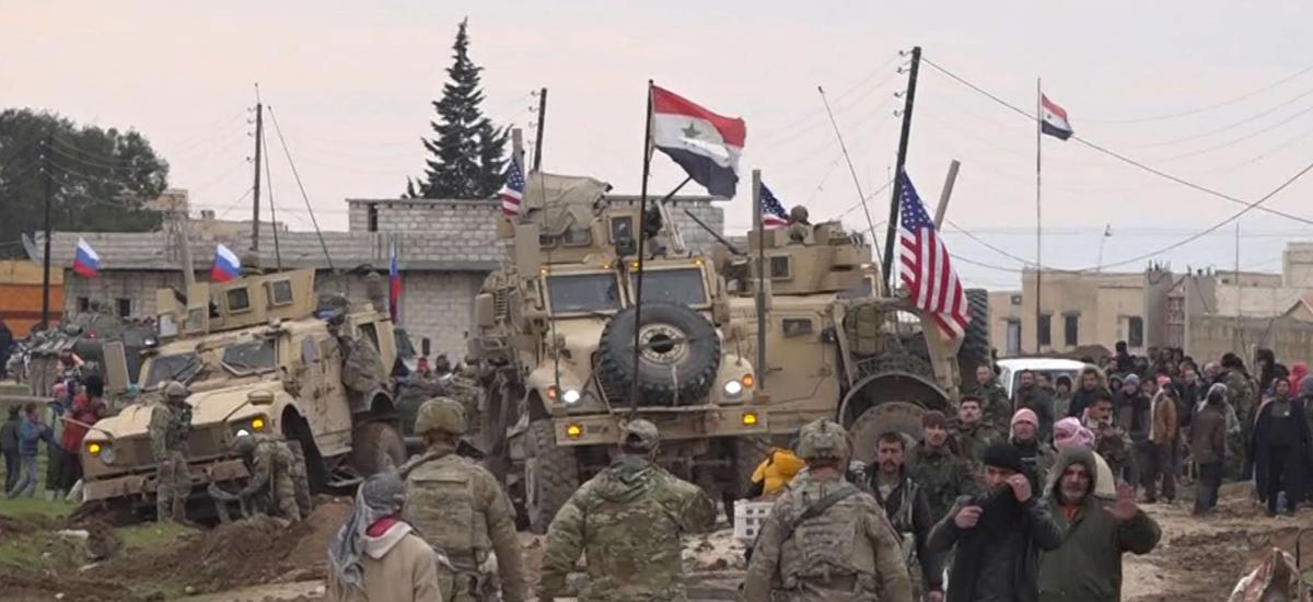 In this frame grab from video, Russian, Syrian and others gather next to an American military convoy stuck in the village of Khirbet Ammu, east of Qamishli city, Syria, Wednesday, Feb. 12, 2020.