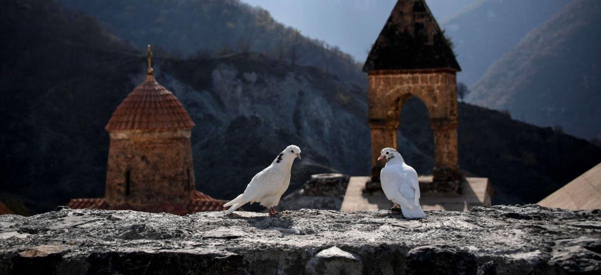 Two white doves stand on a wall of the 12th-13th century Orthodox Dadivank monastery, outside the town of Kalbajar on November 12, 2020, during the military conflict between Armenia and Azerbaijan over the breakaway region of Nagorno-Karabakh. - Kalbajar is one of the seven districts which will be transferred to Azerbaijan as part of a deal on Nagorno-Karabakh. (Photo by Alexander NEMENOV / AFP)