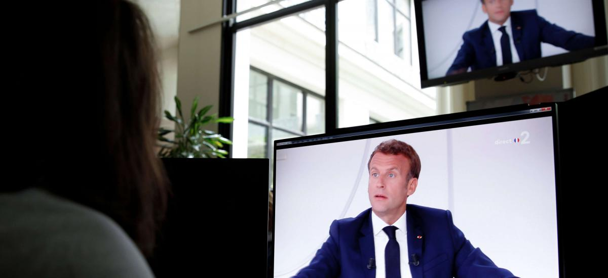 In this file photo taken on July 14, 2020, a woman looks at a TV screen during the traditional televised interview of French President Emmanuel Macron from the Elysee Palace, after the annual Bastille Day military ceremony held on the Place de la Concorde in Paris. - Macron will address French people on November 24, 2020, to announce an adaptation of the lockdown rules, the Elysee palace announced on November 20. (Photo by Stefano RELLANDINI / AFP)