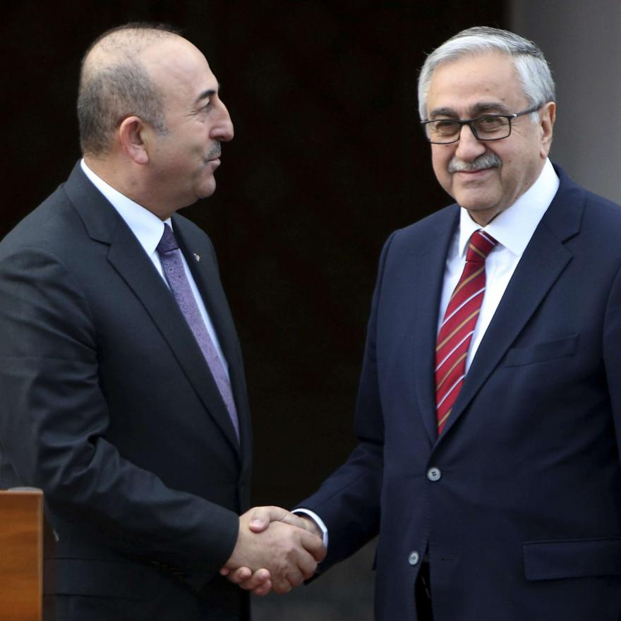Turkish Foreign Minister Mevlut Cavusoglu, left, and Turkish Cypriot leader Mustafa Akinci shake hands after their meeting in the Turkish Cypriot breakaway north part of the divided capital Nicosia, Cyprus, Friday Jan. 25, 2019. AP/Karadjias